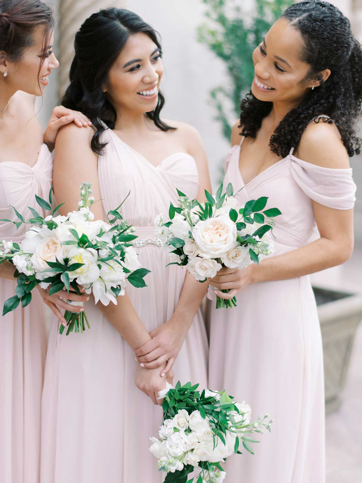 bridesmaids in their blush dresses holding their white bouquets.