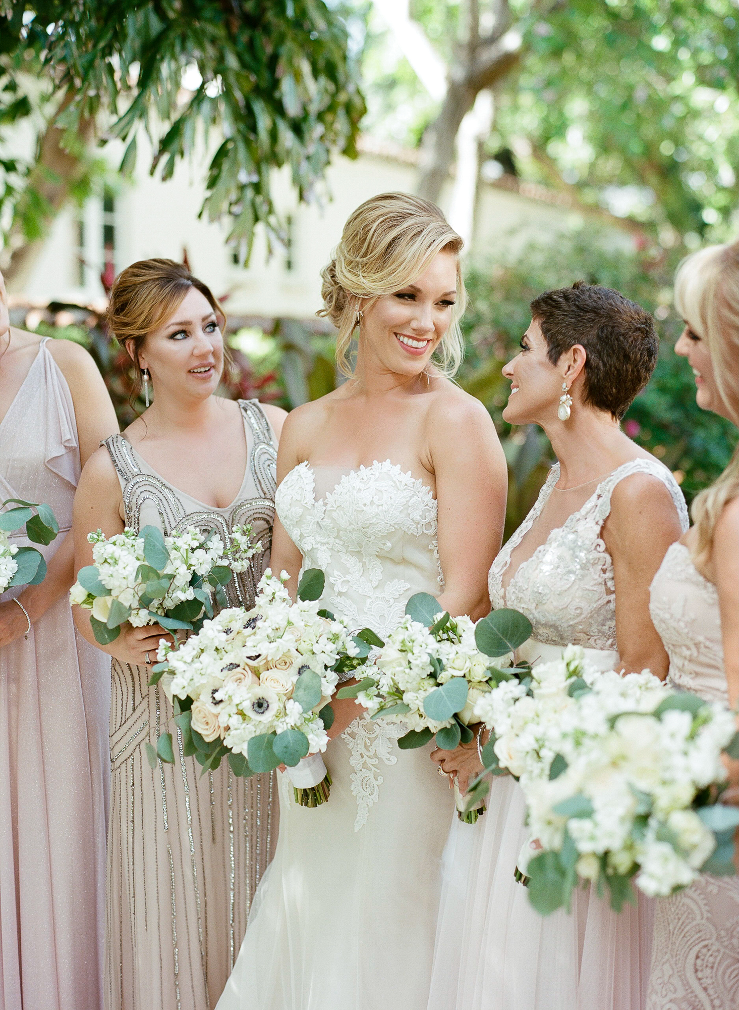 Close-up of bride standing with her bridal party looking at each other wearing blush mix-matched gowns and holding their bouquets.