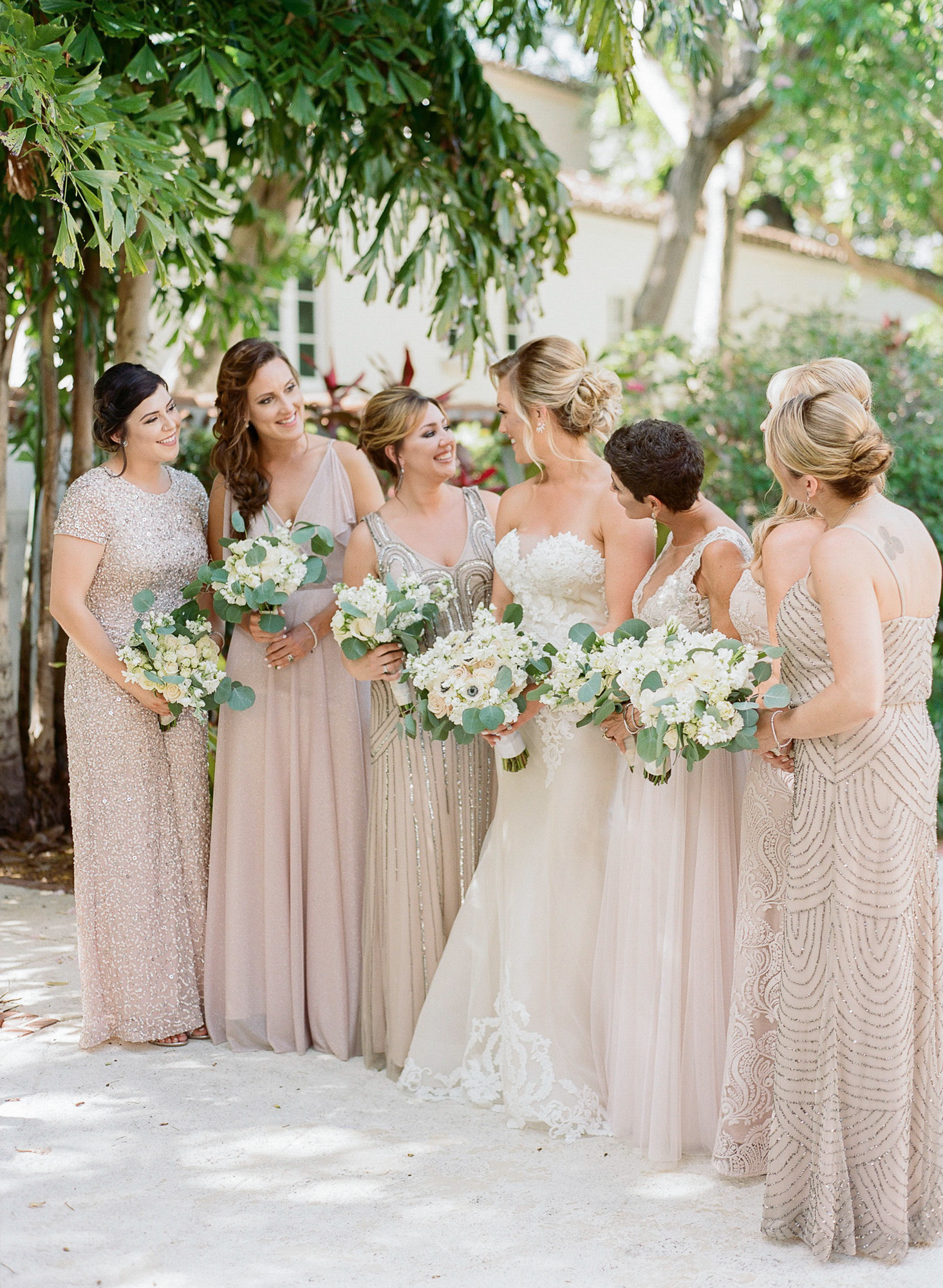 Side photo of bride standing with her bridal party looking at each other wearing blush mix-matched gowns and holding their bouquets.