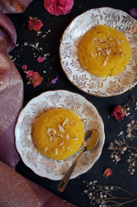 Two white and gold plates with moong dal halwa garnished with almonds