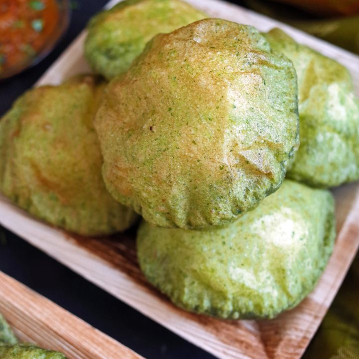 A pile of green spinach Palak Puri on a square leaf plate