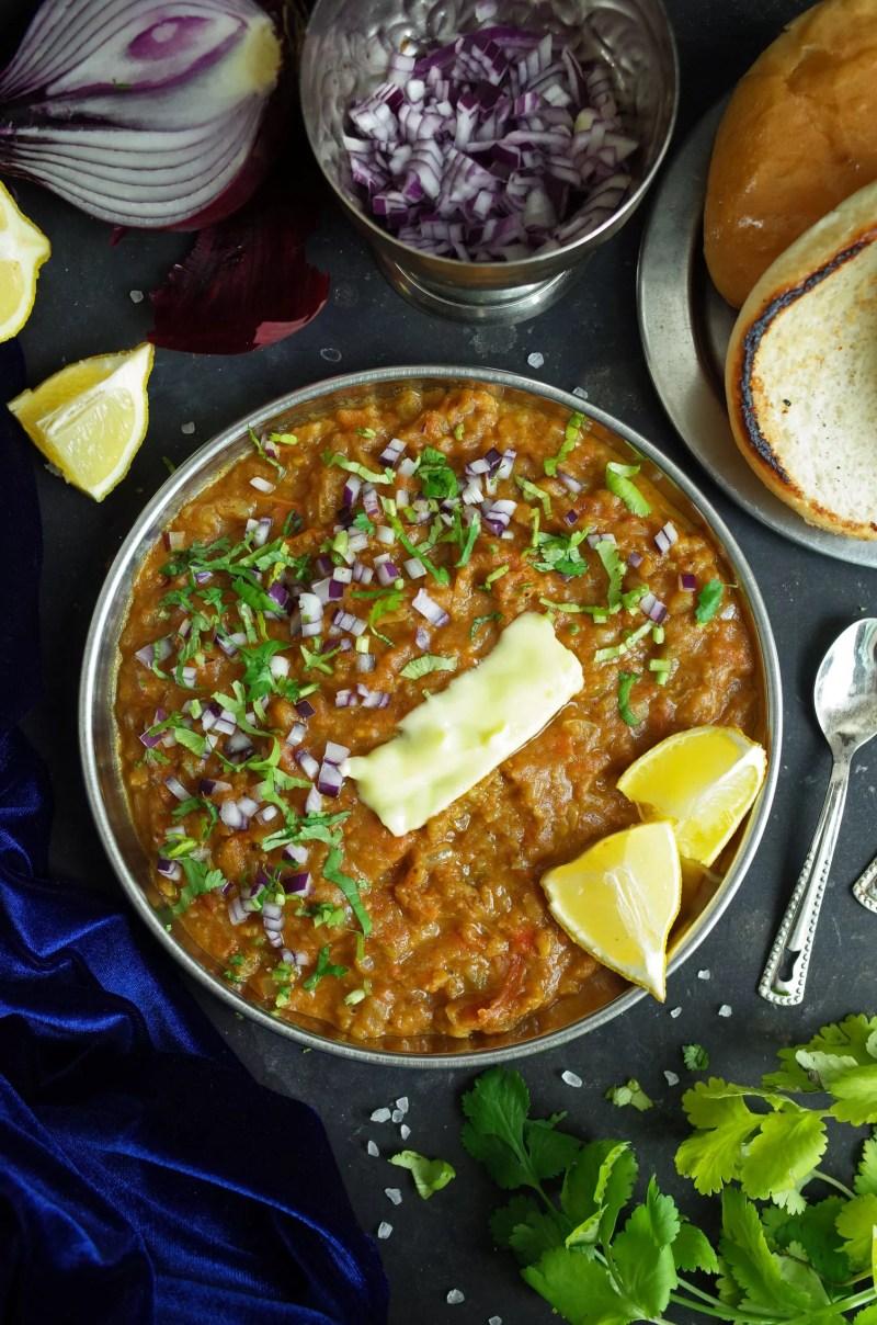 Maharashtrian Pav Bhaji topped with butter, coriander, onion and lemon slices with fresh Pav