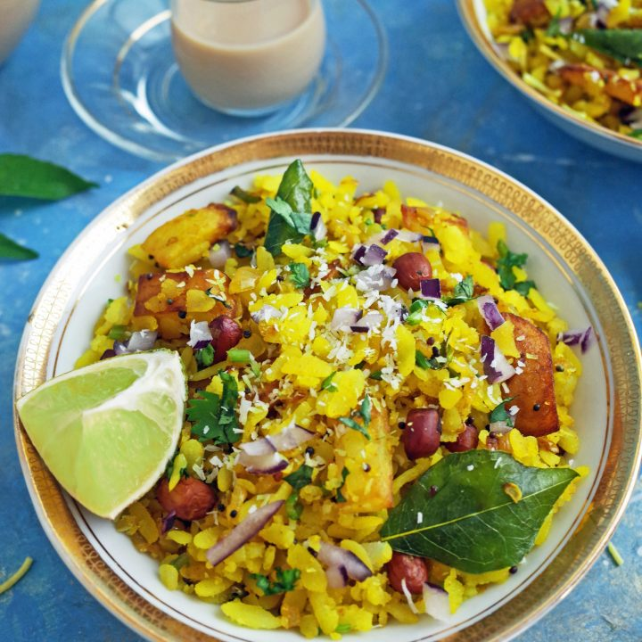 Kanda Batata Poha in a white and gold bowl with Lemon and Chai on a blue background