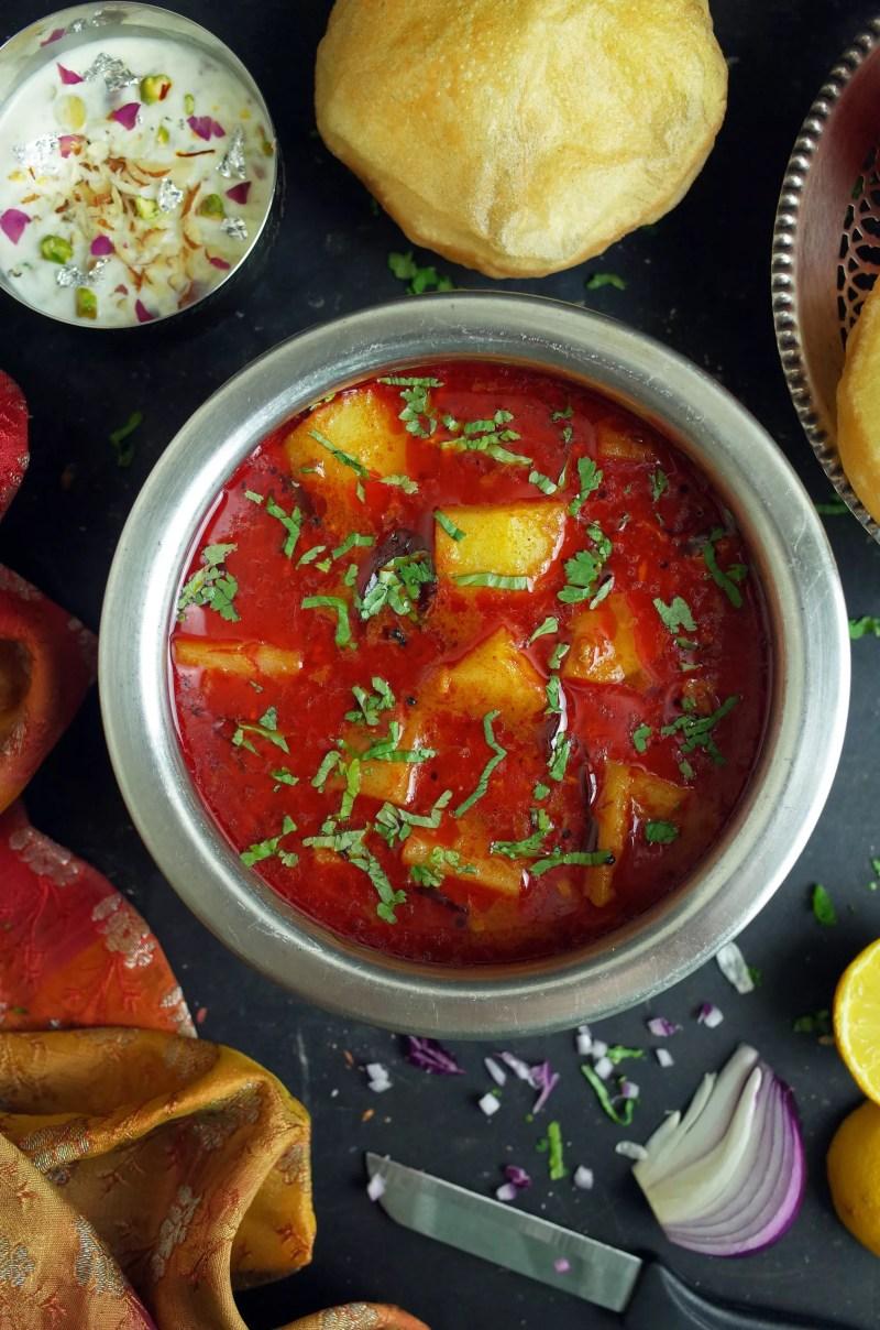 Maharashtrian Batata Rassa Potato Curry in a steel bowl with Puri and Kheer