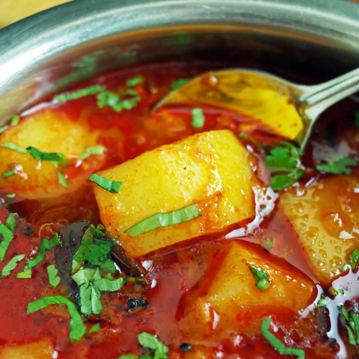 Maharashtrian Batata Rassa / Potato Curry in a steel bowl topped with fresh coriander