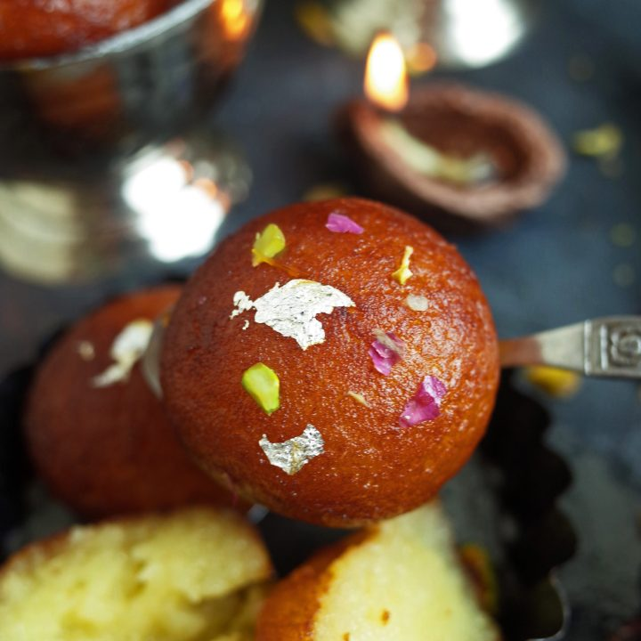 A Gulab Jamun topped with rose petals, pistachios and silver leaf being held on a spoon, with more Gulab Jamun in the background