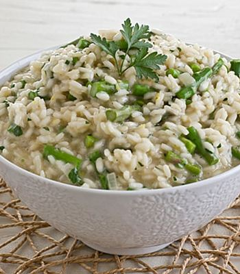 risotto with asparagus and a green garnish in a white bowl