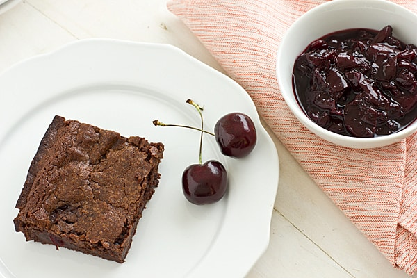 A bowl of cherry sauce sits next to a fresh-baked brownie on a china plate with fresh cherries beside it.
