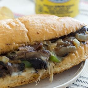 Portabella Cheesesteak sandwich closeup on a white plate