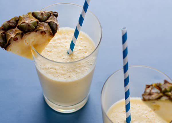 Frothy pineapple smoothies in glasses on a blue surface with blue and white straws