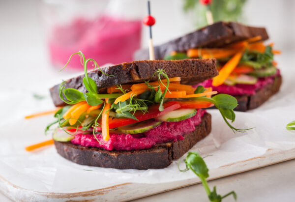 gluten free vegan sandwiches with beet hummus, raw vegetables and sprouts. soft focus