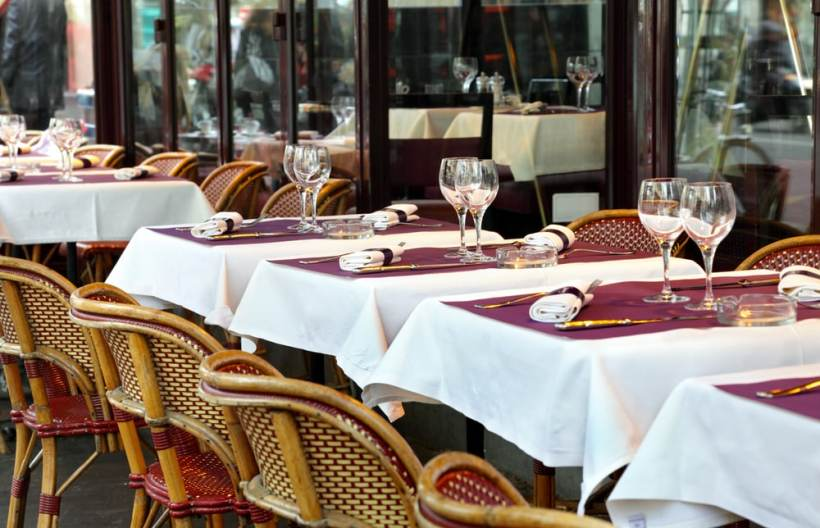 Typical sidewalk restaurant scene in Paris with tables and chairs set for a meal