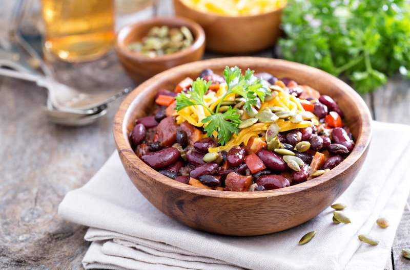 Vegetarian chili with red and black beans, cheddar and pumpkin seeds