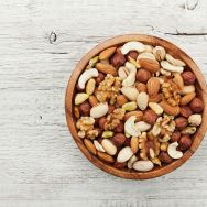 Wooden bowl with mixed nuts on white table from above. Healthy food and snack. Walnut, pistachios, almonds, hazelnuts and cashews.