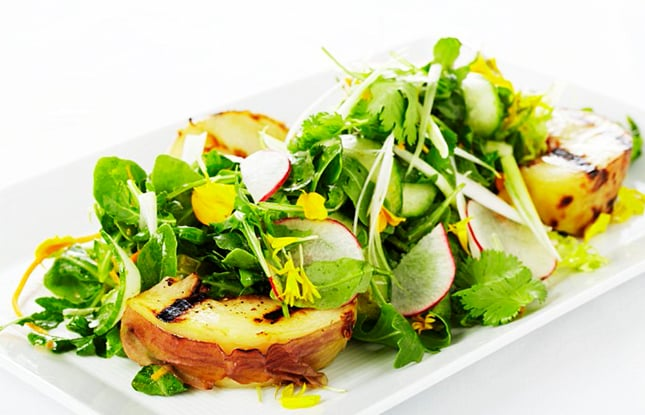 Fresh green arugula piled with grilled pears and thinly sliced raddish on a white rectangular dish