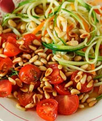 Carrot and Zucchini strips garnished with marinated tomatoes and pine nuts on a white plate