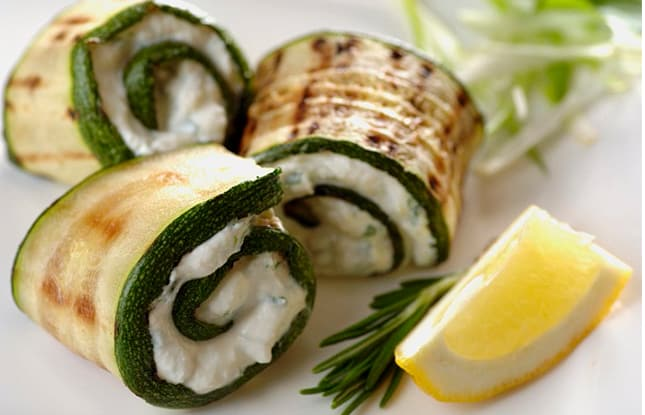 Grilled zucchini strips wrapped around a ricotta-herb filling next to a lemon slice