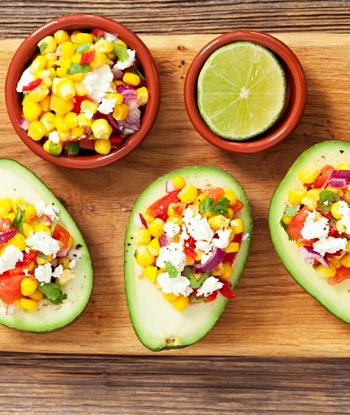 Avocado halves on a wooden cutting board filled with corn salsa and queso blanco cheese