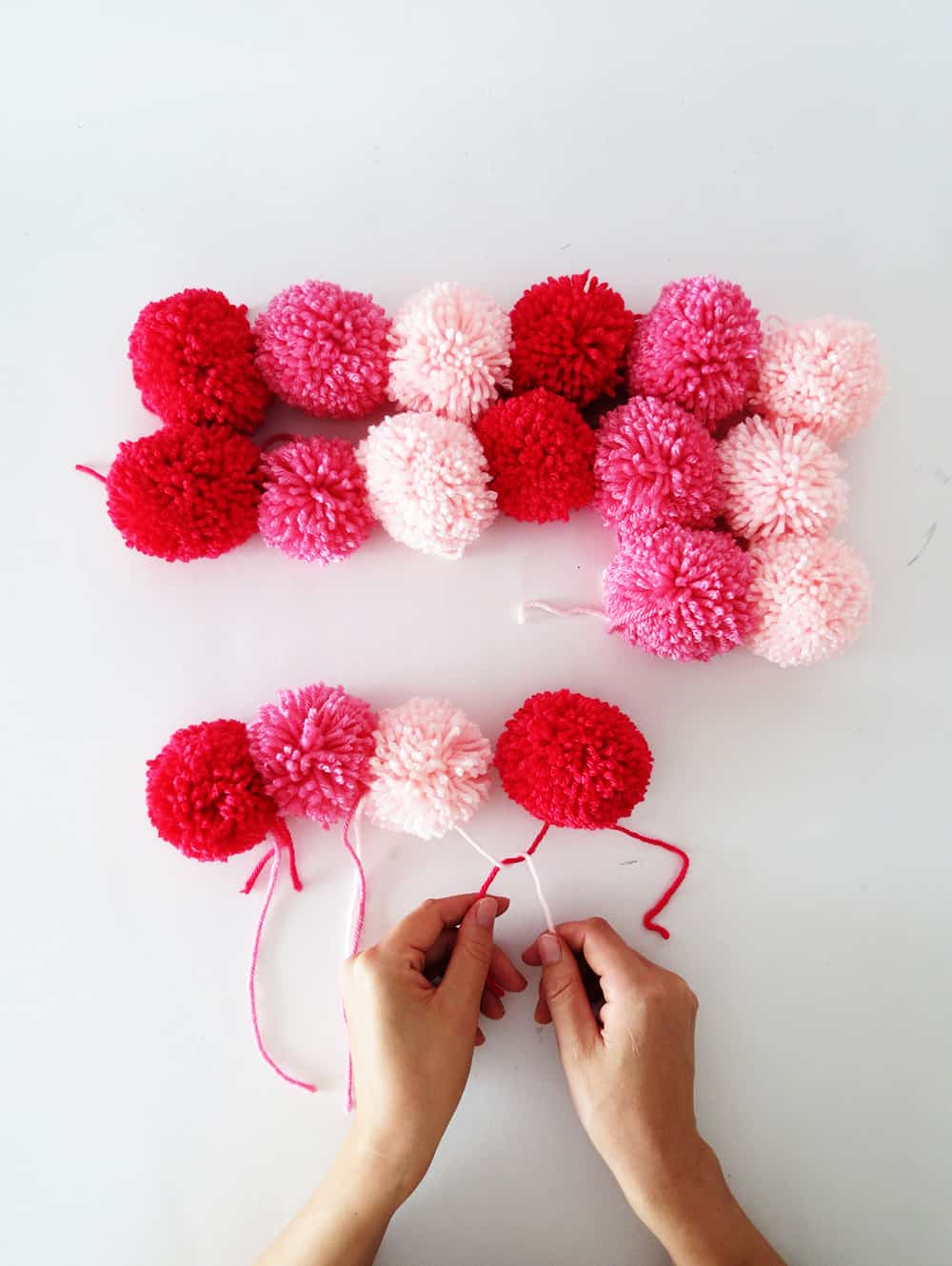 putting the pom poms scarf together