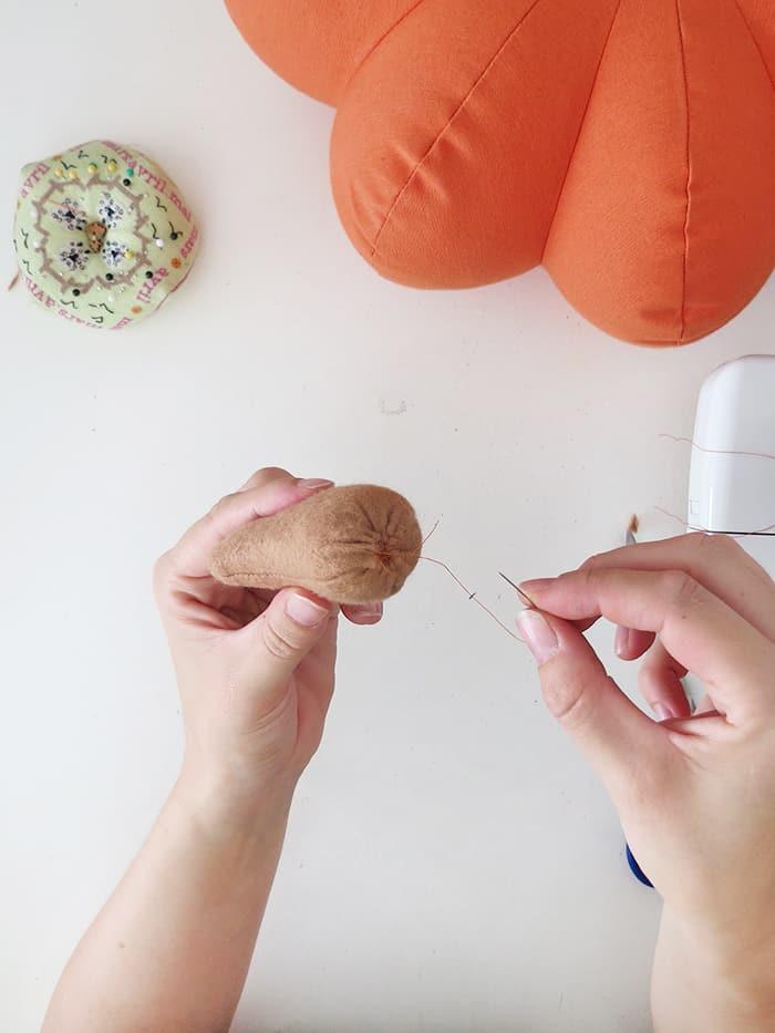 stitch the stem of the pumpkin pillow