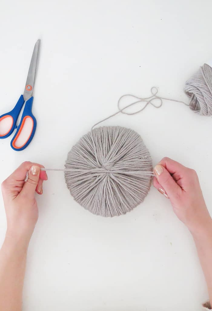 tie a knot to hold giant pom pom together