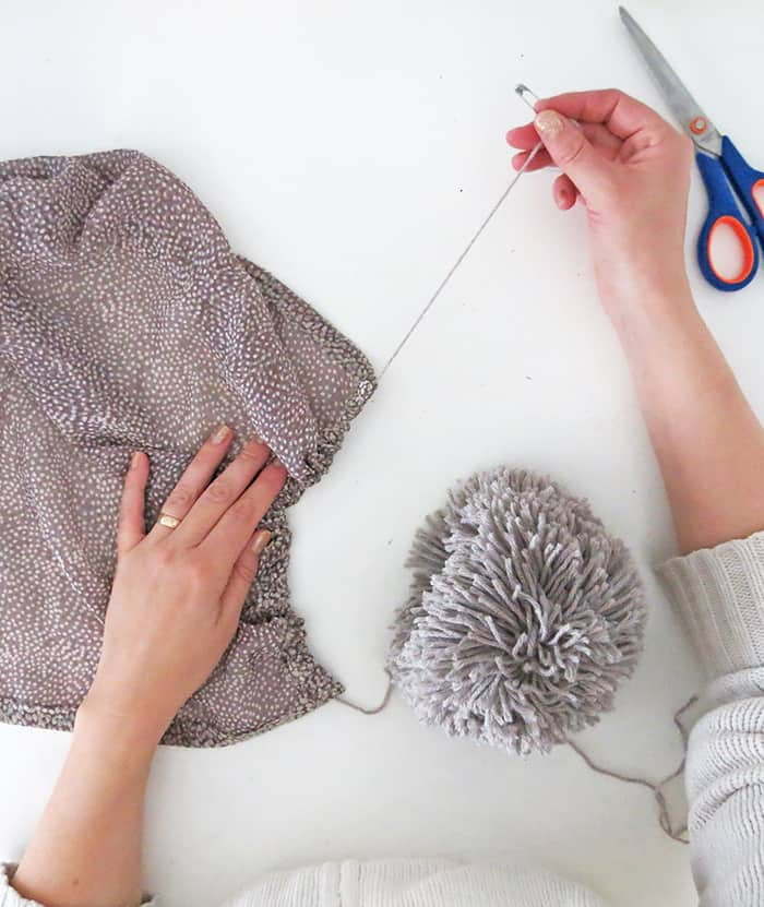 adding pom pom to scarf