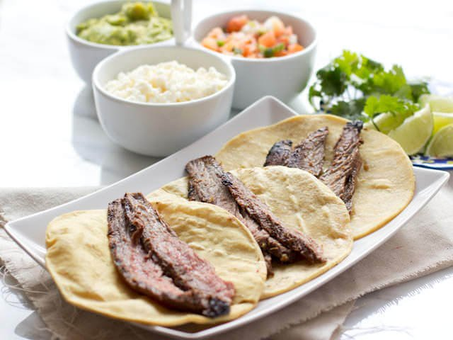 Marinated flank steak on three corn tortillas with three white bowls of authentic carne asada tacos ingredients.