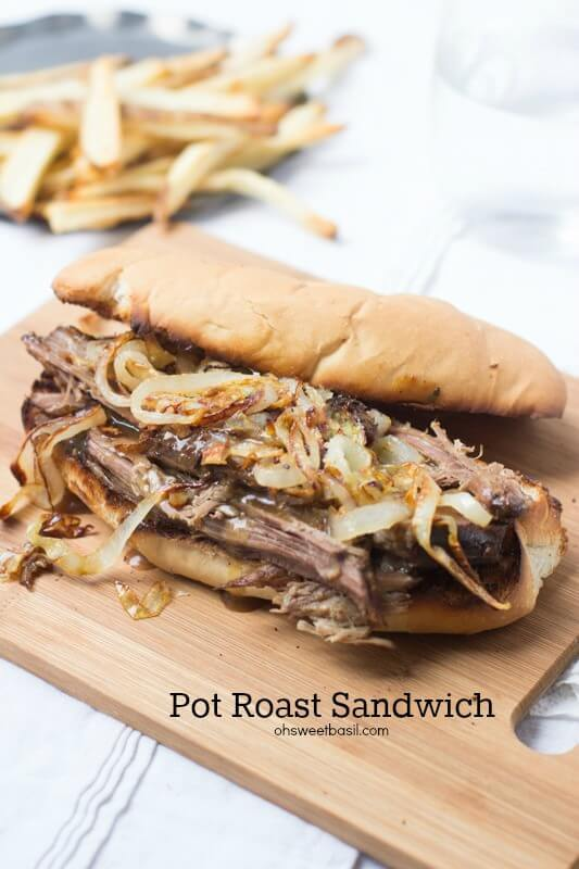 Delicious Pot Roast sandwich with onions on a wooden board.