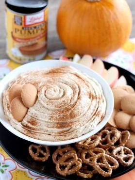 Pumpkin Cheesecake Dip in a white bowl surrounded by pretzels, wafers and sliced apples.