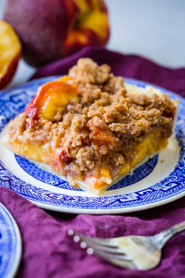 A purple napkin under a vibrant blue china designed dessert plate with a slice of brown sugar peach pie bars