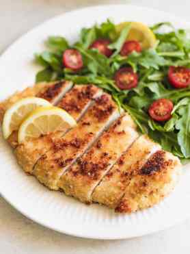 A white dinner plate with sliced, breaded chicken called chicken milanese with a side salad and tomatoes