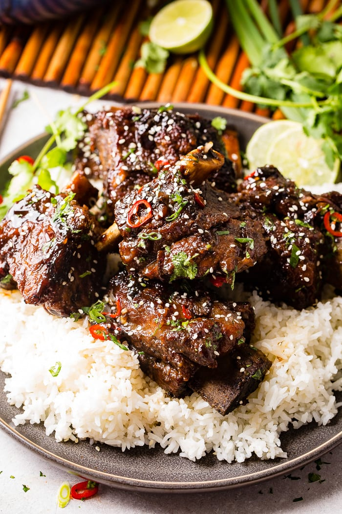 Aphoto of braised short ribs garnished with sesame seeds, cilantro, and red peppers on top of white rice on a gray plate.
