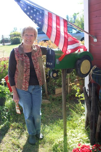 Karen Hansen stands next to her John Deere mailbox to greet us at her home and orchard.
