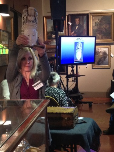Assistants hold up goods while pictures flash onto the big screens at the Case Antiques auction