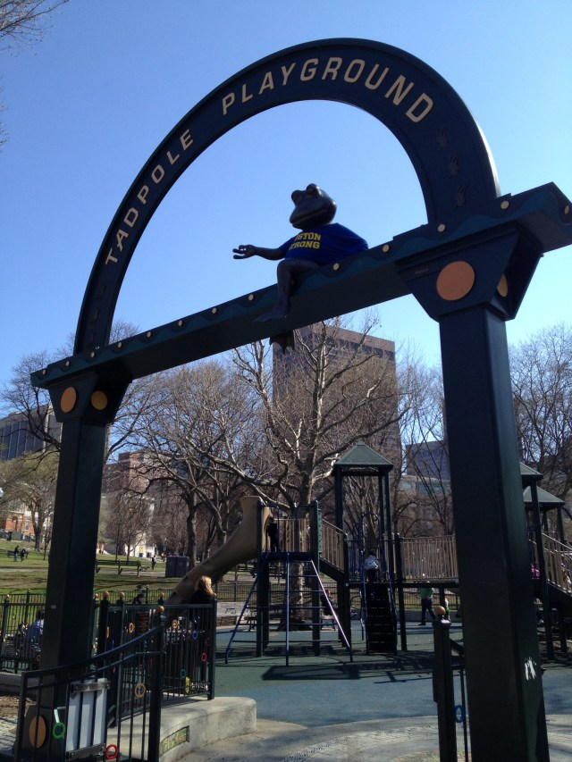 Frog wearing Boston Strong t-shirt sits on top the entry arch at Boston Commons playground