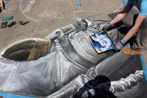 Working from a picture, Shane Sandberg adds exquisite detail to his astronaut chalk drawing.