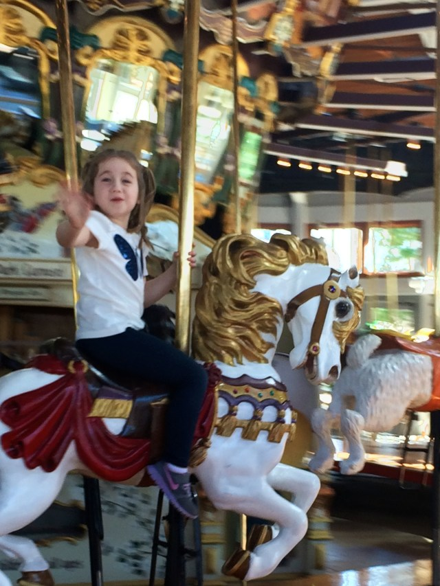 Riding a fancy steed at the Coolidge Park Antique Carousel, Chattanooga, Tennessee.