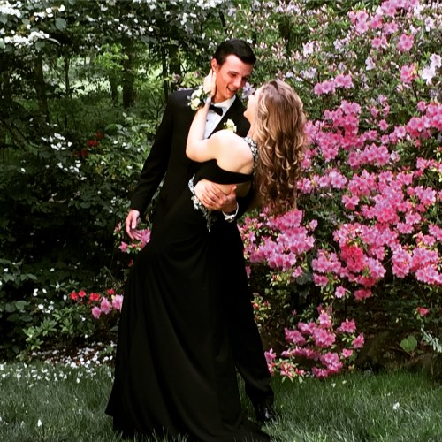 Couple dressed for the Prom pose for pictures in front of the springtime azaleas in Suzie Hall's garden.
