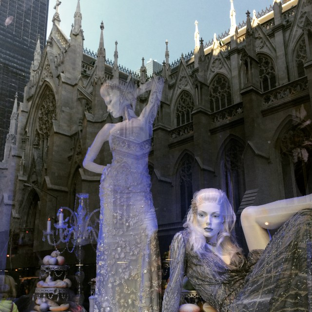 """Two sensuously posed models seem ironically """"surrounded"""" by a reflection of St. Patrick's Cathedral."""