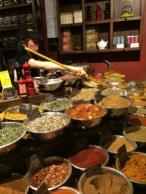 A retailer scoops up spices for a bulk order inside Spices and Tease at Chelsea Market.