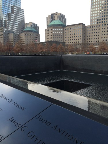 A cityscape frames the pools of water at 9/11 Memorial Museum.