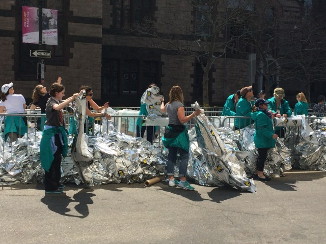 Volunteers organize the mylar capes, getting ready to put them on the first finishers of Boston Marathon 2016.