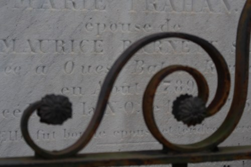 Artful ironwork frames delicate carving on this tomb at St. Louis Cemetery 1