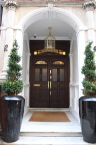 Brass adornments and topiaries set this door apart from the others.