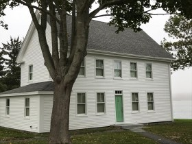 Standing sideways on the lot to catch the water view is this clapboard home with green door on Water Street.