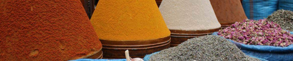 Cones of spices form a backdrop for open bags garlic and crushed ingredients.