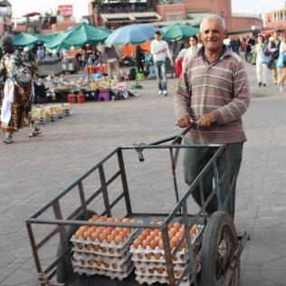 An egg salesman moves past other stalls making deliveries