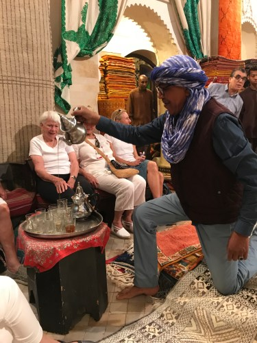 A salesman pours mint tea in dramatic Moroccan fashion for customers.