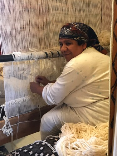 A weaver pauses to show us her work.