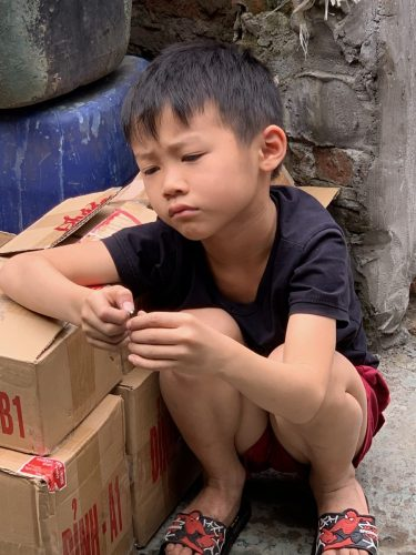 Vietnam boy, bored at brass factory